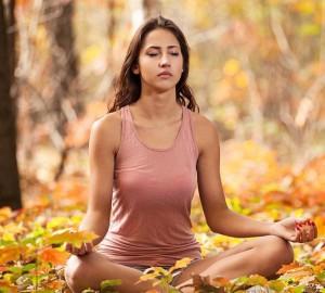 Ung kvinne mediterer i skogen