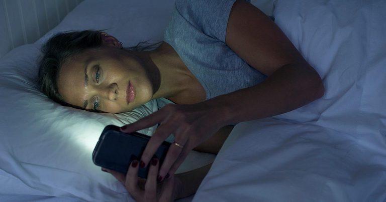 I sengen med mobilen