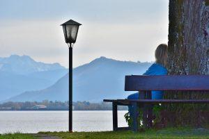 Kvinne sitter og mediterer ved et tre